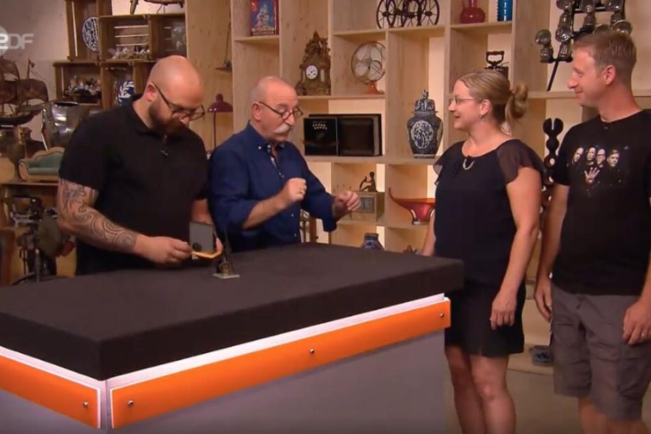 Experte Sven Deutschmanek, Moderator Horst Lichter und das Ehepaar Hahn warten auf die Expertise zu den beiden Blechspielzeugen.