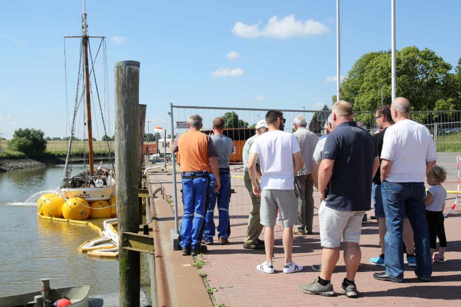 """Schaulustige verfolgen die Arbeiten auf dem Segelschiff """"No. 5 Elbe"""", das am Pier in Stadersand liegt. In der letzten Nacht wurde das Schiff mittels Luftkissen gehoben."""
