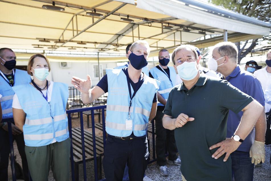 Armin Laschet (vorne, r., CDU), Ministerpräsident von Nordrhein-Westfalen, während er im Flüchtlingslager Moria mit Frontex-Mitarbeitern spricht.