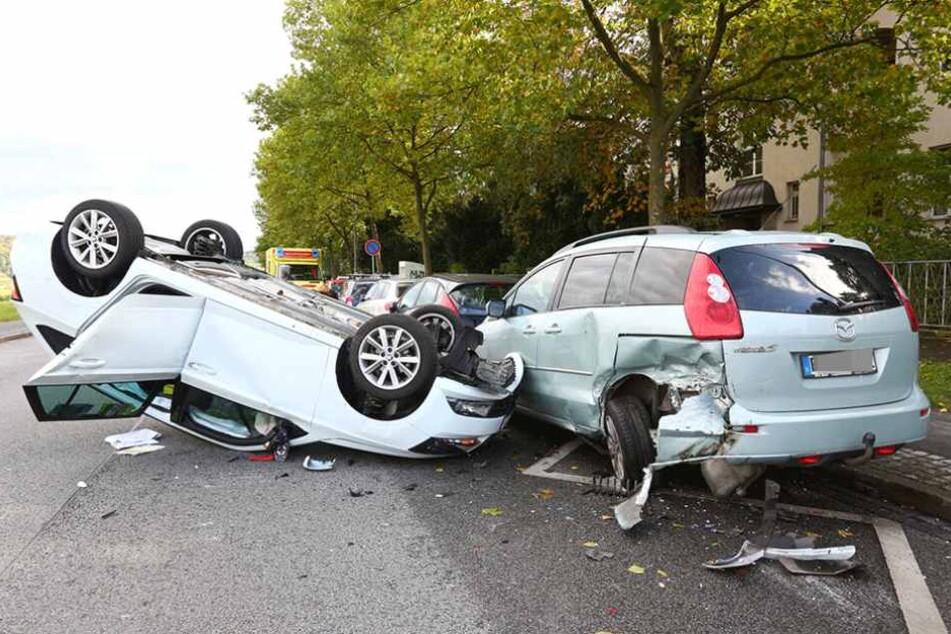 Der Skoda liegt auf dem Dach, deutlich erkennbar ist die schwere Beschädigung des Mazdas am linken Hinterradbereich.