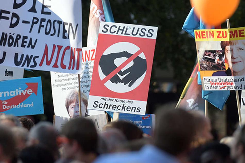 """Ostdeutschland ist gespalten: """"Nein zu Merkel"""", """"Die AFD-Pfosten gehören nicht zu uns"""" oder """"Schluss mit der Raute des Schreckens"""" sind auf einigen Plakaten zu lesen."""