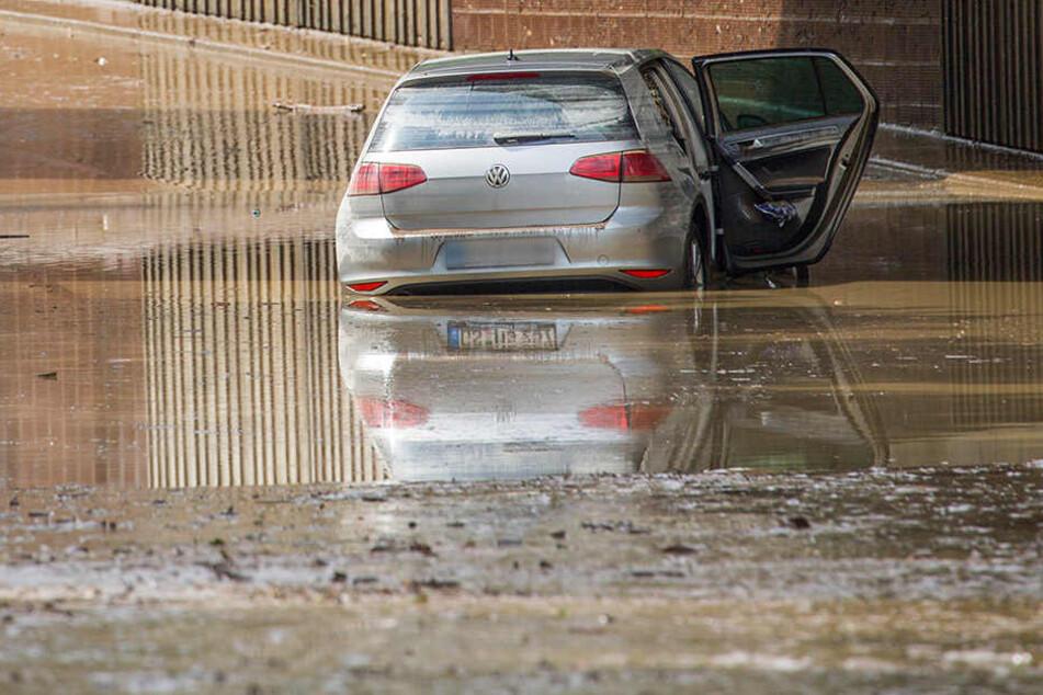 Ein Auto ist im Wasser stecken geblieben. Die komplette Straße ist in Schlamm getränkt.