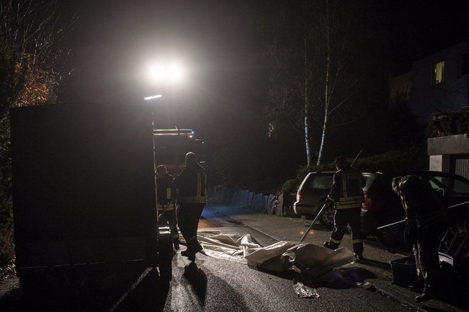 Feuerwehrmänner packen am 11.11.2017 in Wilnsdorf ein Zelt zusammen, das am Tatort von der Polizei genutzt worden war.