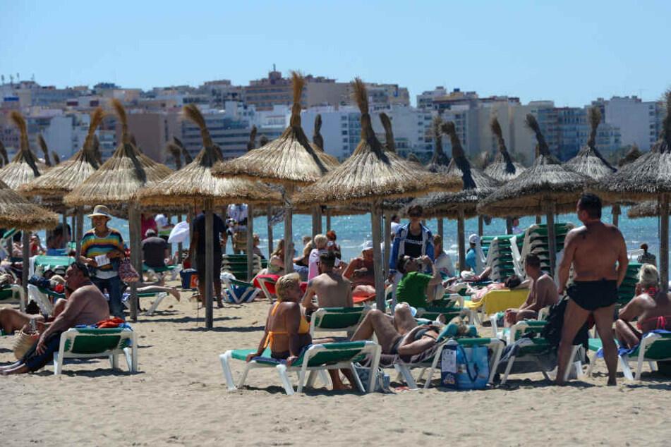 Touristen sonnen sich am Strand von Playa de Palma. (Archivbild)