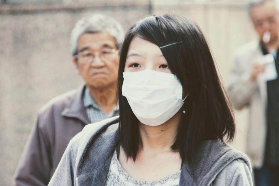 Ein Mundschutz bei Grippepatienten verringert die Ansteckungsgefahr für Andere.
