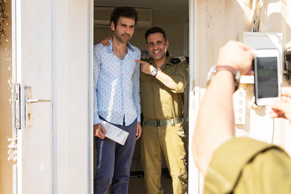 """Salam Abbass (l.Kais Nashif) muss am Checkpoint bei Kapitän Assi Tzur (Yaniv Biton) als """"Promi"""" auch für ein Foto herhalten."""