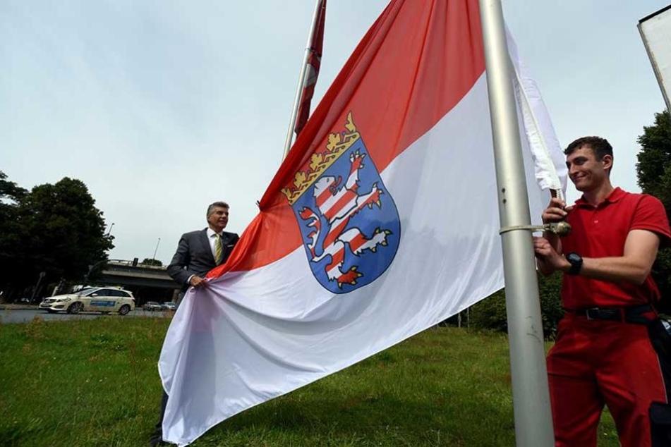 Der stellvertretende Bezirksbürgermeister Carsten Engelmann (l) und der Mitarbeiter des Bezirks, Stephan Böttcher hissen die hessische Fahne am Jakob-Kaiser-Platz.