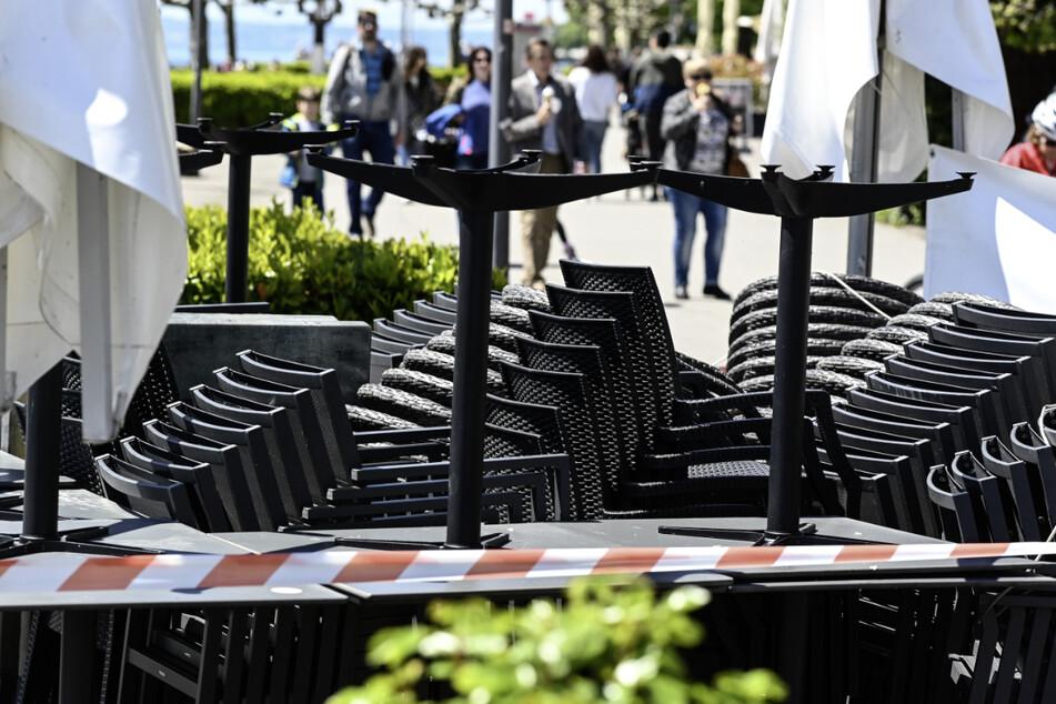 Stühle und Tische stehen aufgereiht an der Uferpromenade, während im Hintergrund Passanten laufen. Der Inzidenzwert ist noch zu hoch, sodass die Außengastronomie im Bodenseekreis nicht öffnen kann.