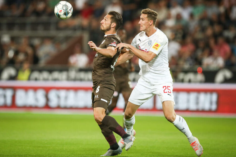 Mit seinem Körper schirmt der Stürmer den Ball vor seinem Gegenspieler ab.