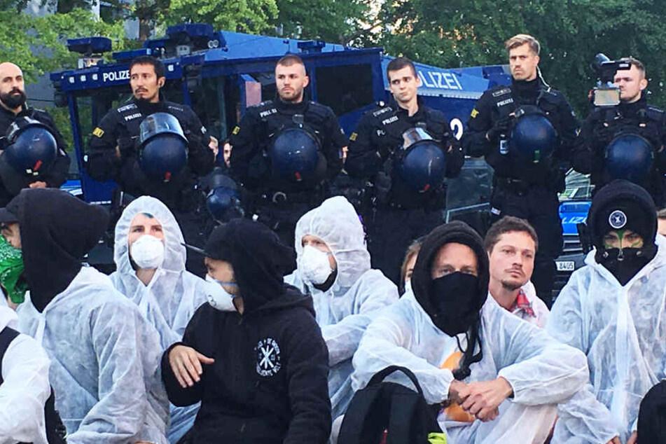 Das Foto zeigt Protestierende und Polizisten vor dem Eingang zum Frankfurter Messegelände. Im Hintergrund ist ein Wasserwerfer zu sehen.
