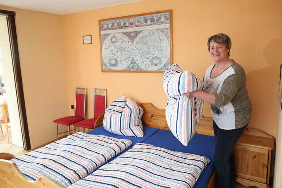 Weltkarte überm Bett: Marlies Hempel schüttelt in einem ihrer beiden Pilgerzimmer die Kissen auf.