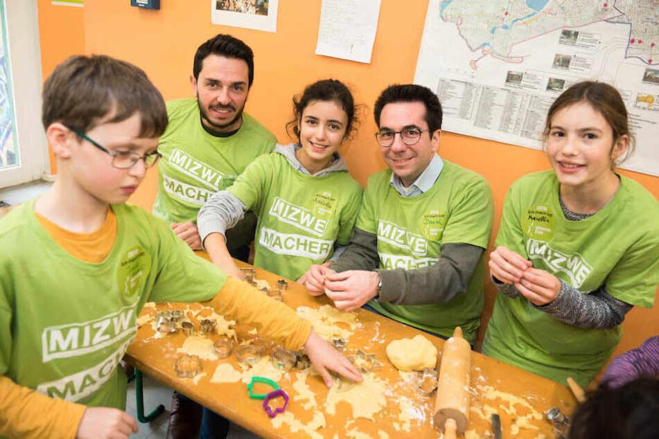 Dervis Hizarci (KIgA.) und ZdJ-Geschäftsführer Daniel Botmann (34, re.) mit backenden Kindern in Berlin.