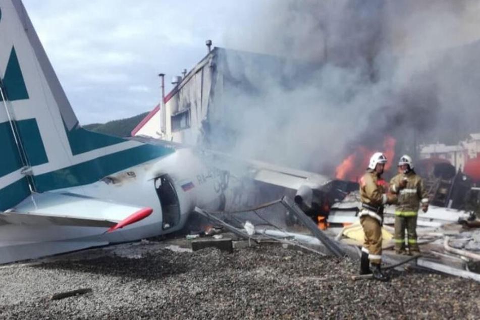 Feuerwehrleute löschen das brennende Flugzeug.