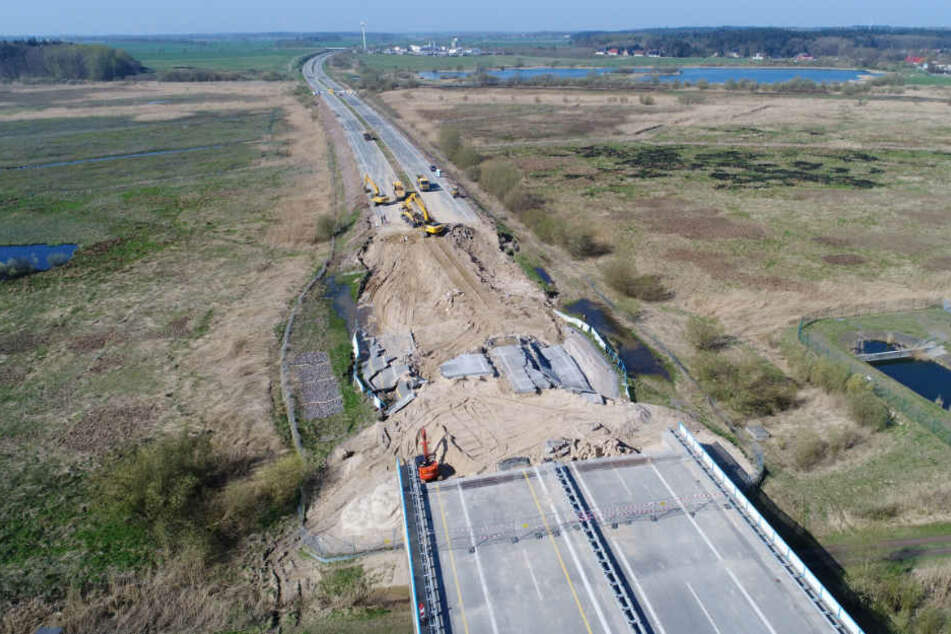 Bagger arbeiten am Rückbau des Straßendammes an dem zerstörten Teilstück der Autobahn A20.