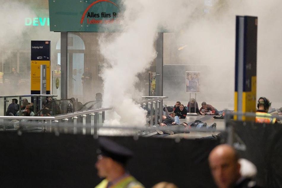 Komparsen spielen im Rahmen der Anti-Terror-Übung auf dem Boden liegende Verletzte.