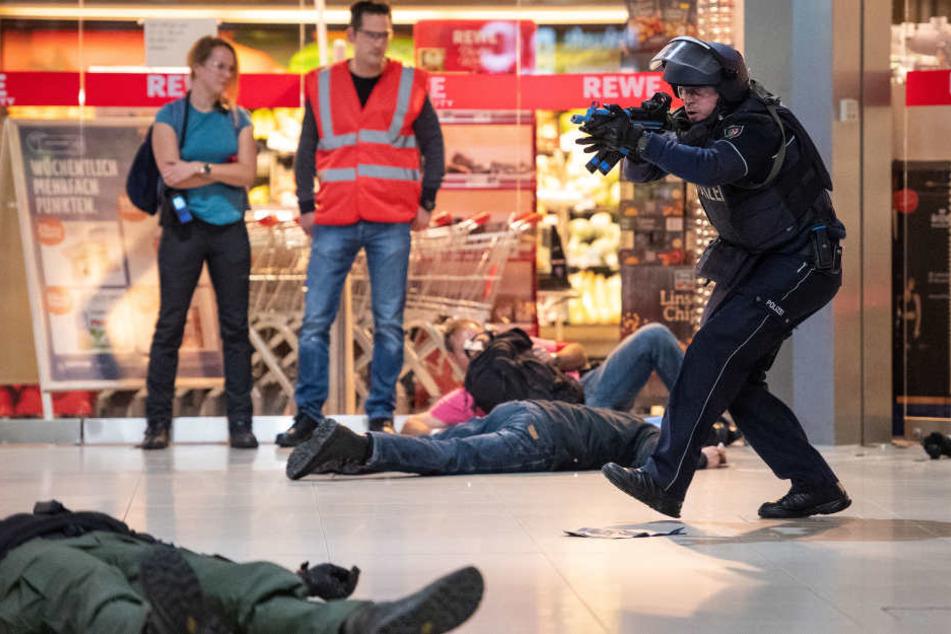 Polizisten gehen während einer Anti-Terror-Übung am Flughafen Köln/Bonn gegen angenommene Terroristen vor. Im Hintergrund stehen Beobachter der Übung.