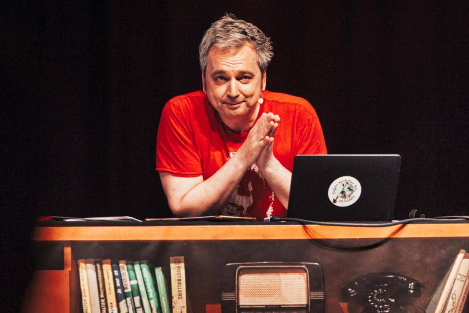 Arnd Zeigler wie man ihn kennt. Hinter seinem Schreibtisch führt er durch die Sendung.