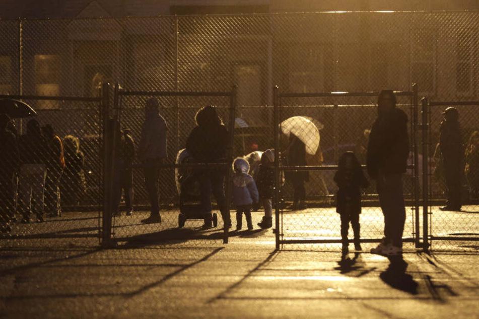 Kinder warten auf dem Schulhof der Whitney M. Young Jr. Community School darauf, von ihren Eltern abgeholt zu werden, nachdem die Schule aufgrund einer Schießerei abgeriegelt wurde.