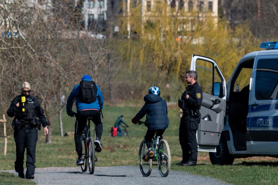 Polizisten stehen zur Beobachtung an einem Radweg an der Elbe.