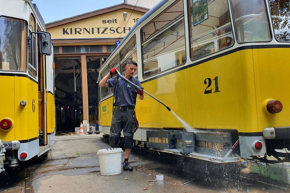 Ein Mitarbeiter der Kirnitzschtalbahn befreit die Bahnwagen mit dem Hochdruckreiniger vom Schlamm.