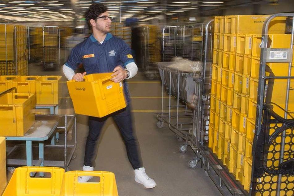 Der Flüchtling Anas Almalla stapelt im Briefzentrum der Deutschen Post Postkisten.