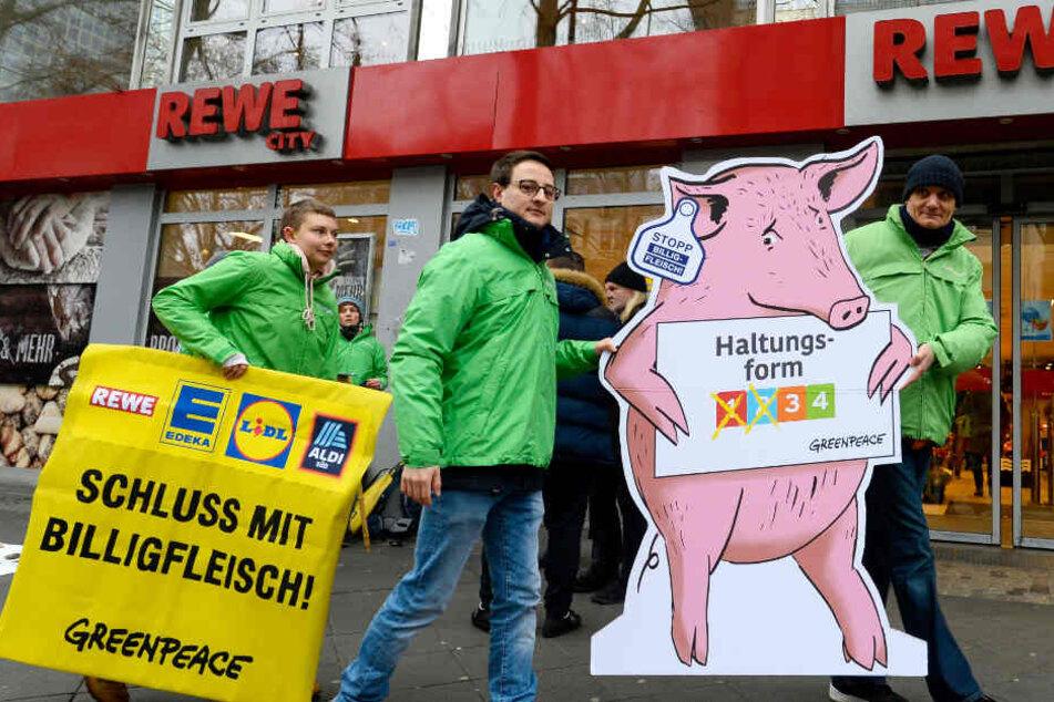 Greenpeace-Aktivisten protestieren vor einem REWE-Lebensmittelgeschäft gegen Billigfleisch.