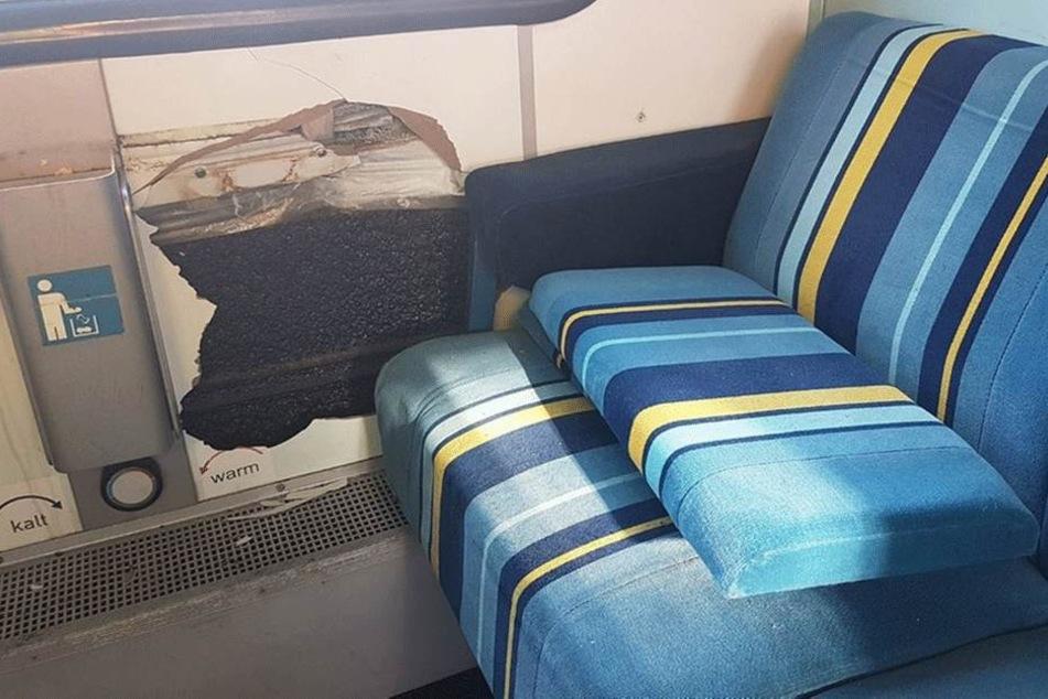 In der Wandverkleidung wurde diese Loch getreten, auf der Sitzbank liegt eine abgerissene Rückenlehne.