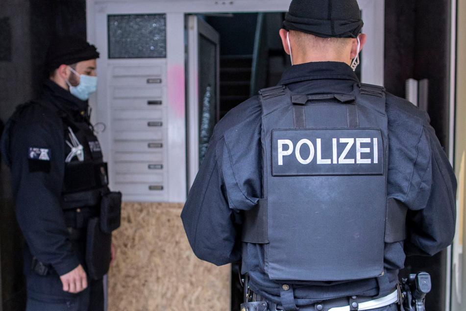 Polizisten stehen bei einer Razzia vor einem Hauseingang. (Symbolbild)
