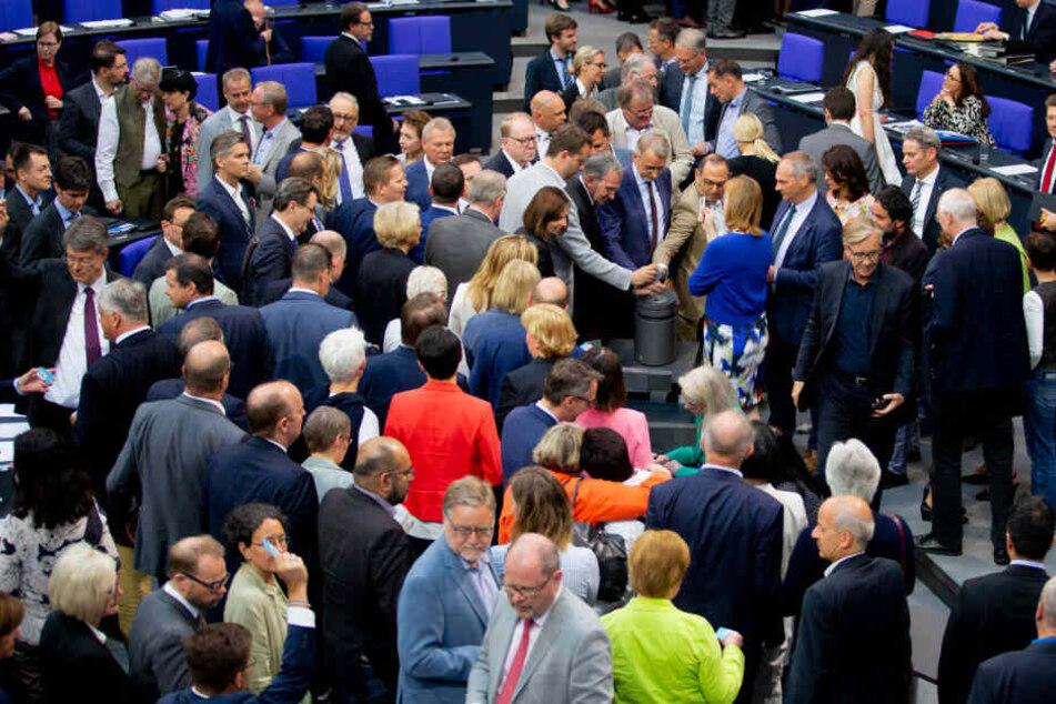 Mitglieder des Deutschen Bundestages stimmen im Plenum im Bundestag an einer Urne zum Asyl- und Aufenthaltsrecht ab.