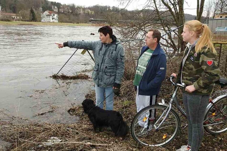Familie Müller schaut besorgt auf den vollen Fluss in Grimma.
