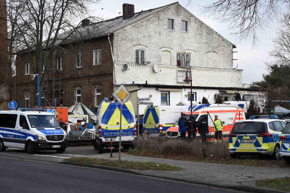 Einsatzkräfte der Polizei und Rettungsdienst stehen vor einem Haus.