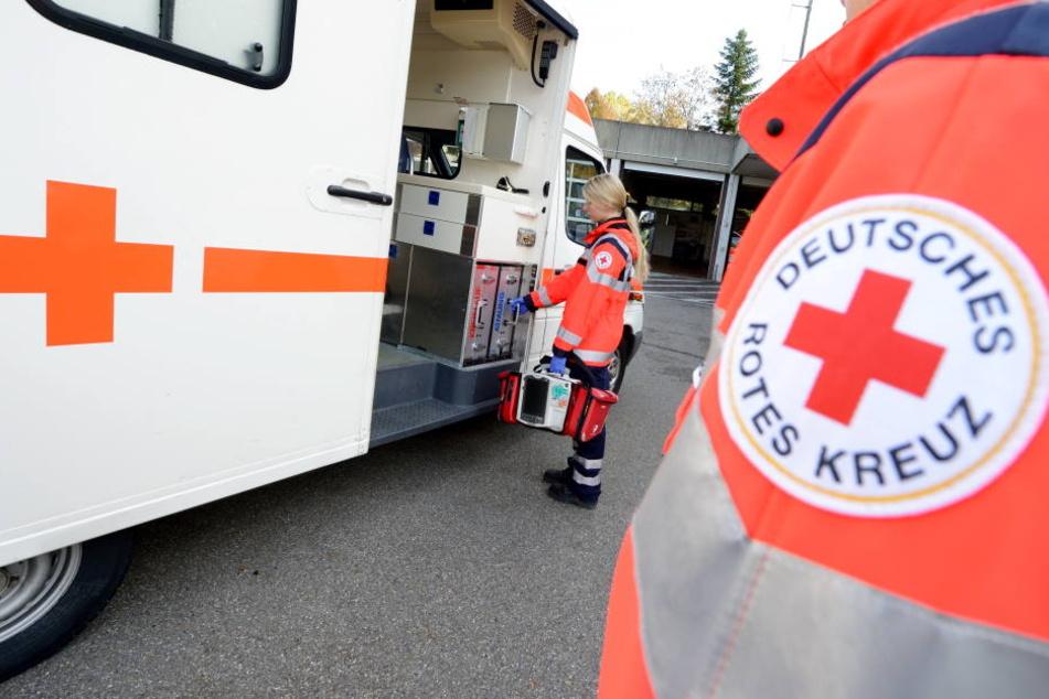 Eine Rettungssanitäterin steht vor einem Rettungswagen des Deutschen Roten Kreuzes. (Symbolbild)
