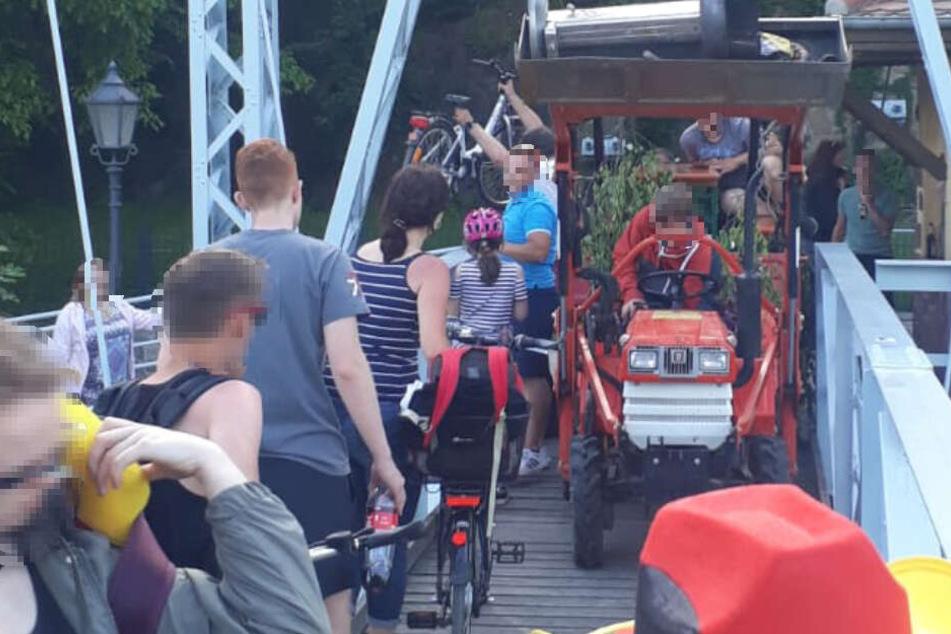 Der rote Minitraktor quetscht sich über die schmale Brücke, an der linken Seite wird ein Fahrrad vorbeigehoben.