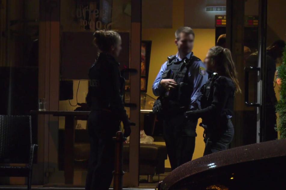 Einsatzkräfte der Polizei stehen vor dem Lokal.