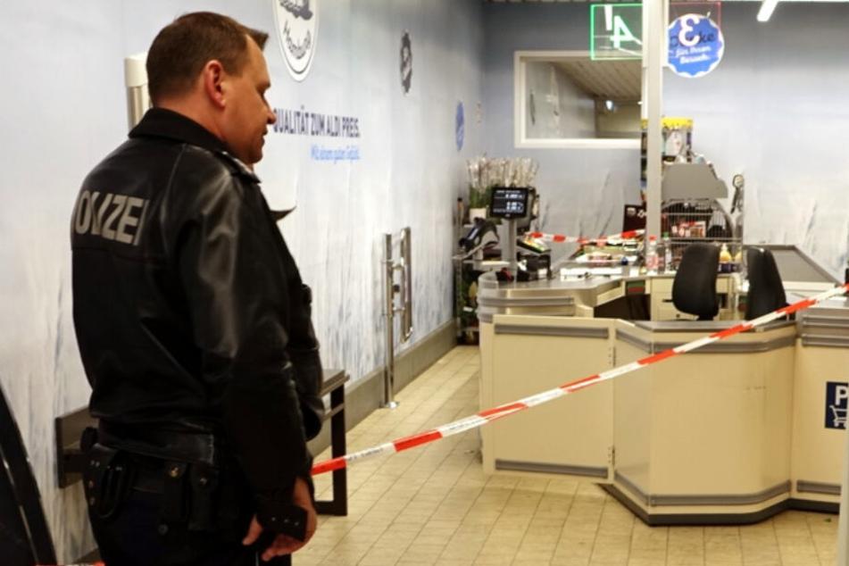 Ein Polizist steht vor einem Absperrband am Tatort.