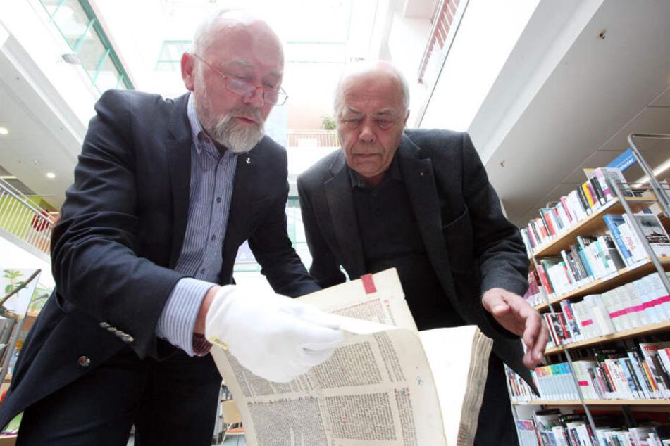 """Steffen Jacob (62, l.) von der Spenderfirma """"Punkt 191"""" und Curt Bertram (72) vom Förderverein blättern in der restaurierten """"Consilia""""."""