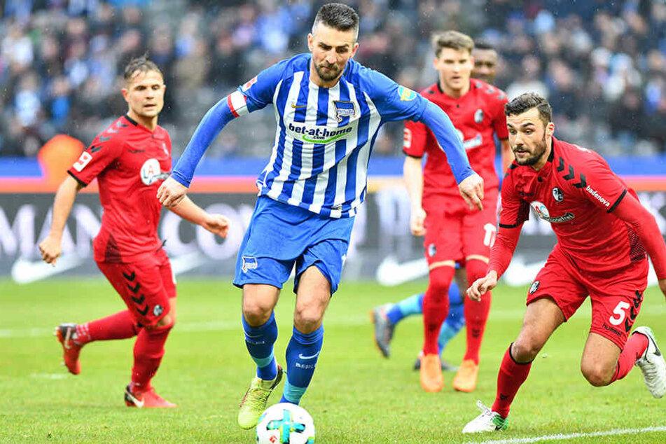 Herthas Vedad Ibisevic (M) und Freiburgs Manuel Gulde kämpfen um den Ball.