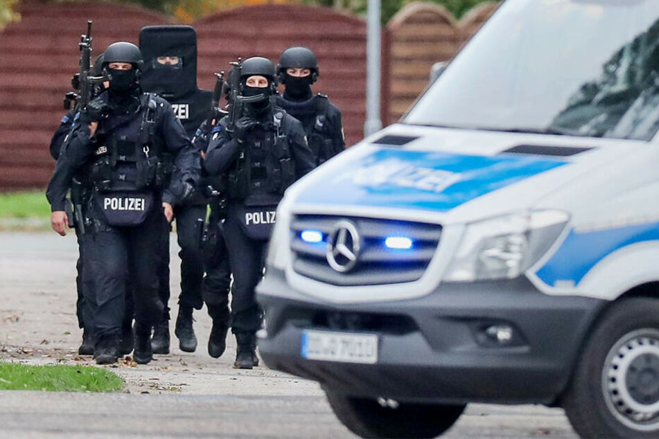 Polizisten gehen bewaffnet durch den Ort Wiedersdorf/Landsberg. Neben den Schüssen in Halle hat es auch Schüsse im rund 15 Kilometer entfernten Landsberg (Saalekreis) gegeben.