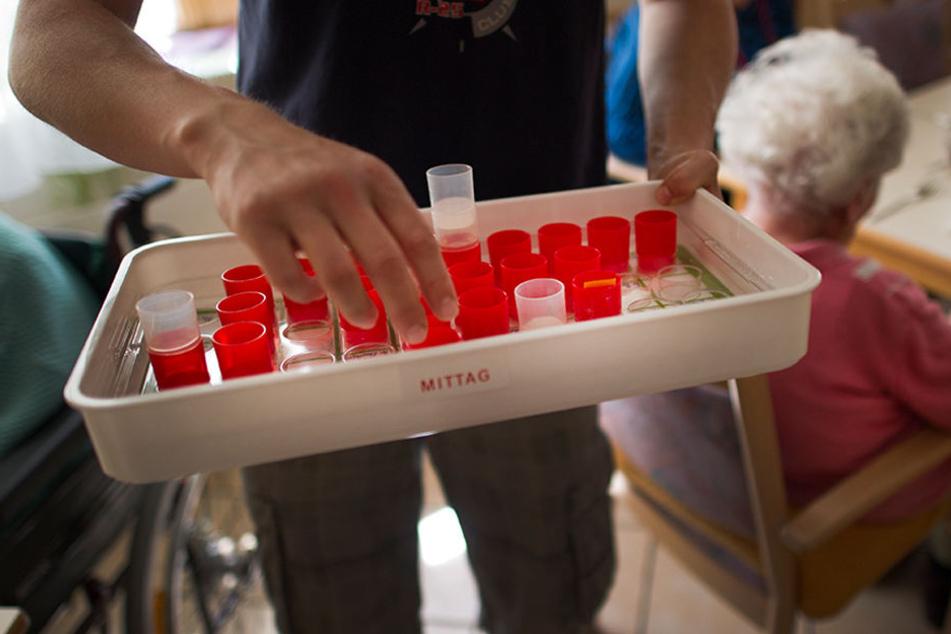 Medikamente werden vor dem Mittagsessen von einem Pfleger verteilt.