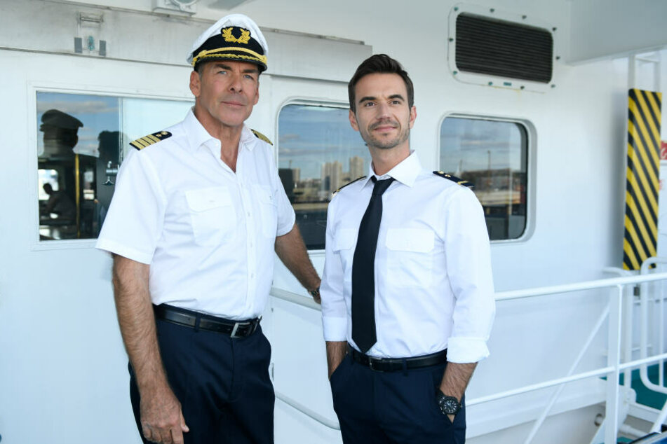 """Alt und neu: Kapitän Burger (Sascha Hehn, l) und der junge Offizier Florian (Florian Silbereisen) stehen in der Folge """"Das Traumschiff: Tansania"""" auf der Brücke des Schiffs."""