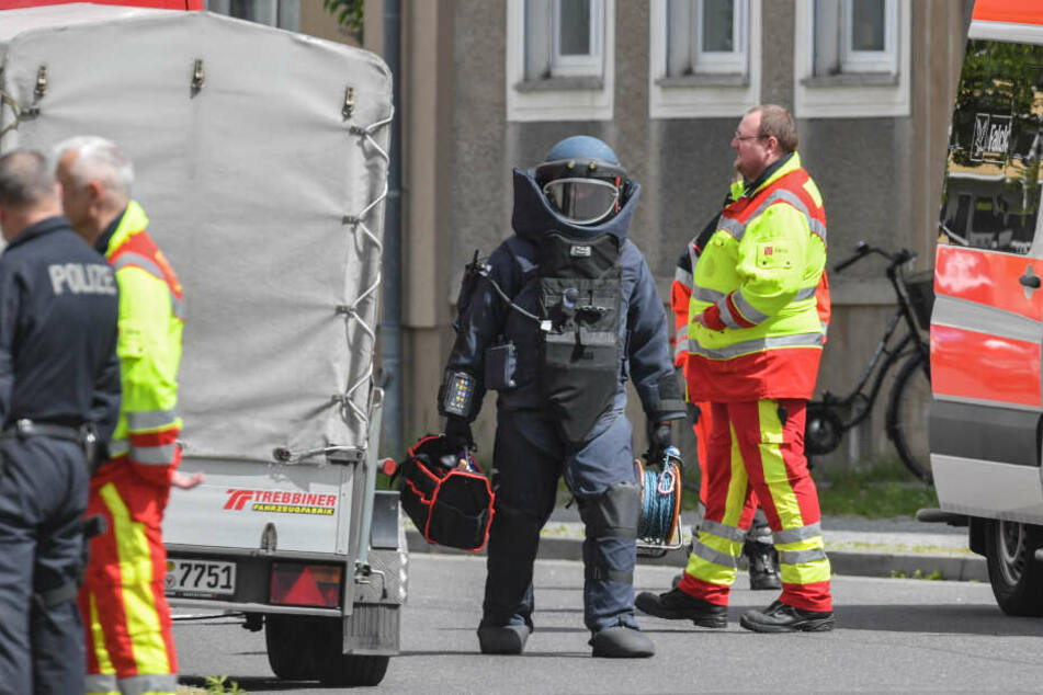 Ein Sprengstoffexperte geht in Schutzausrüstung über die gesperrte Amtstraße.