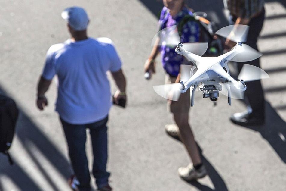Eine Drohne fliegt über Menschen in der Stadt. So manchem ist diese Technik ein Dorn im Auge.