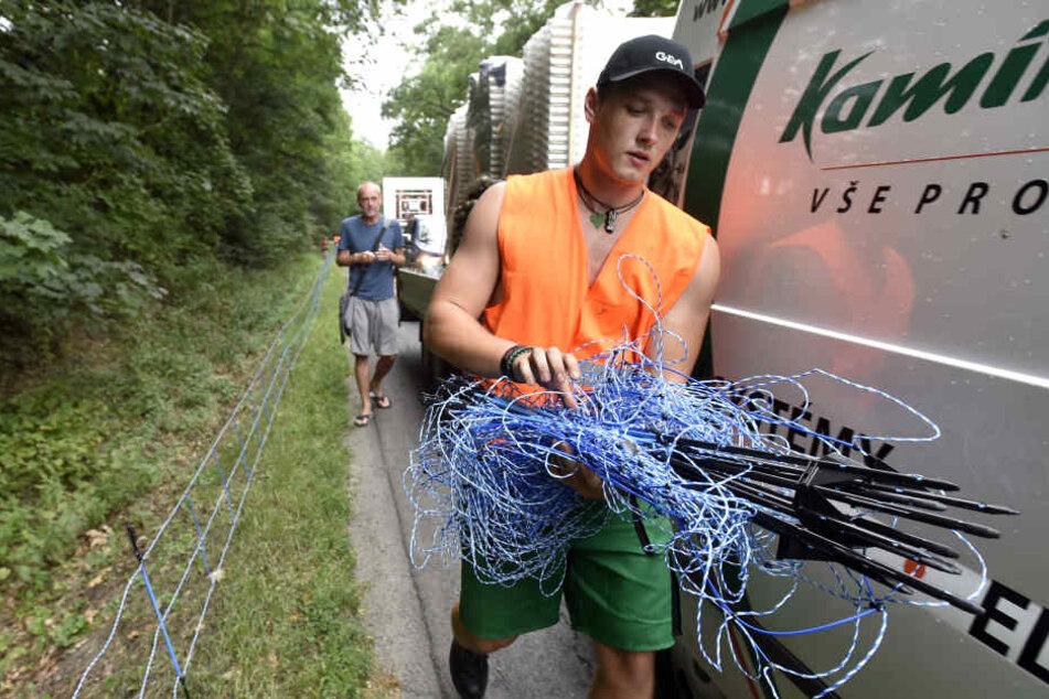 Straßenarbeiter stellen einen Elektrozaun entlang einer Landstraße bei Zlin (Tschechien) auf.