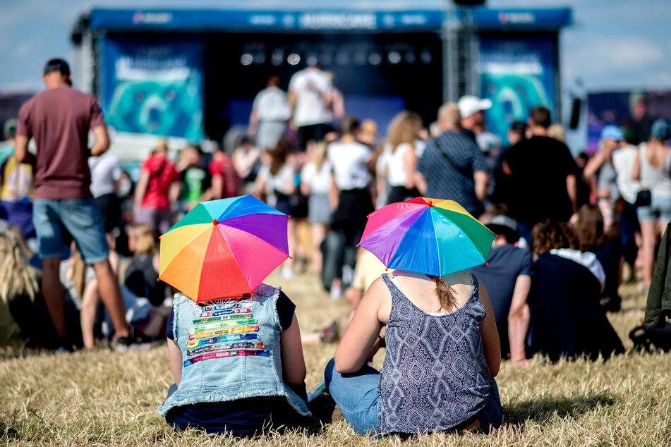 Zwei junge Frauen mit bunten Schirmen auf dem Kopf hören auf dem Hurricane Festival einem Konzert zu.