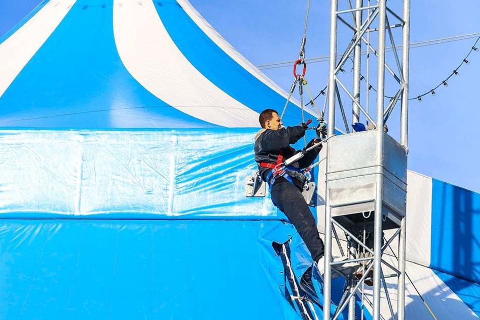 Job mit Aufstiegschancen: Ein Circusmitarbeiter dichtet in luftiger Höhe Mast und Zeltdach ab.