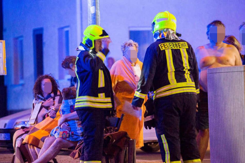 Die geretteten und evakuierten Personen standen wenig bekleidet im Freien und wurden mit Decken aufgewärmt..