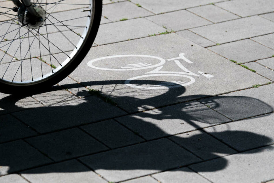 Eine Frau fährt mit ihrem Fahrrad an einem Fahrrad-Symbol vorbei.