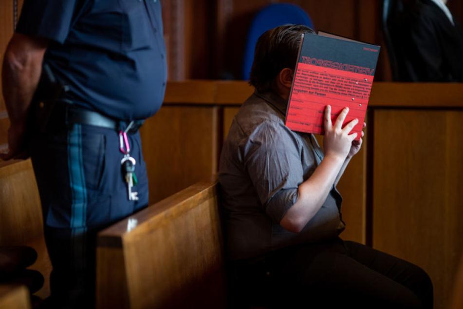 Ein 22-jähriger Angeklagter hält sich im Landgericht Nürnberg-Fürth einen Ordner vor sein Gesicht.
