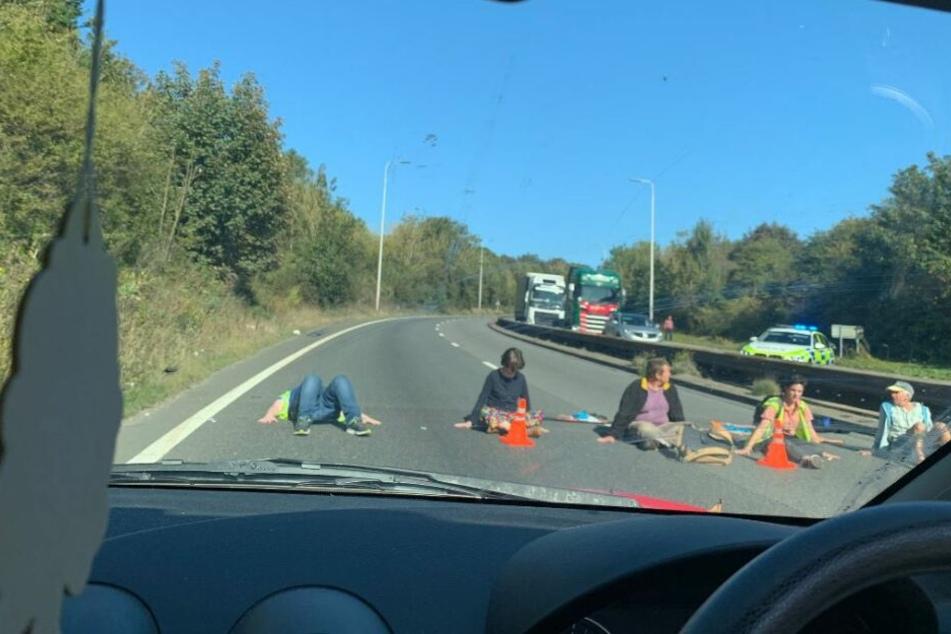 Fünf Demonstranten kleben freiwillig an der Autobahn fest.