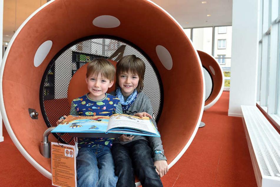 Leo (6) und Toni (9) finden die bequemen Audio-Sessel in der Kinderabteilung  der Bibliothek klasse.
